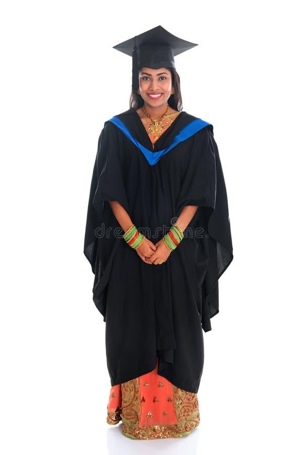 Estudante universitário indiana feliz do corpo completo no vestido da graduação imagem de stock