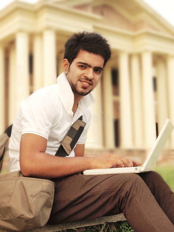 Estudante universitário indiano que trabalha no portátil. fotos de stock royalty free
