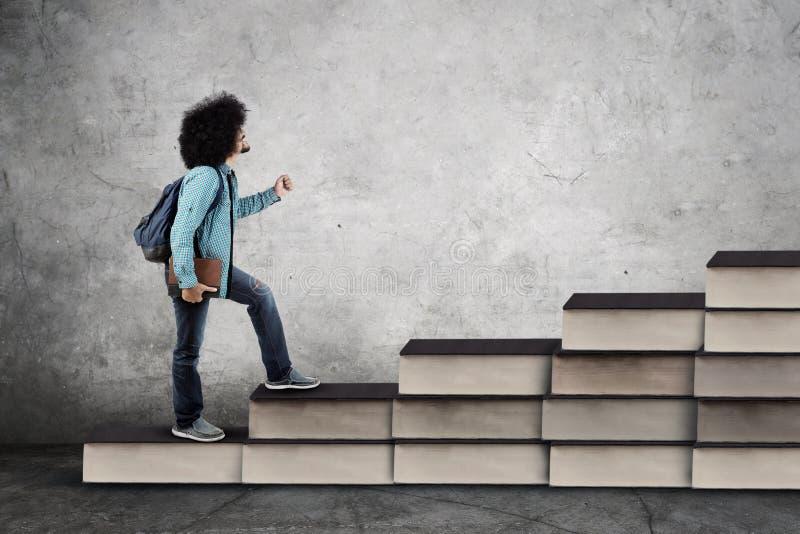 A estudante universitário masculina do Afro anda na escada dos livros fotografia de stock