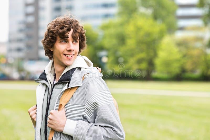 Estudante universitário masculina nova de sorriso no terreno da faculdade foto de stock royalty free