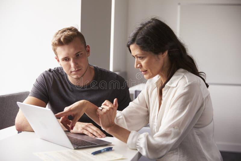 Estudante universitário masculina Working One To um com tutor fotos de stock