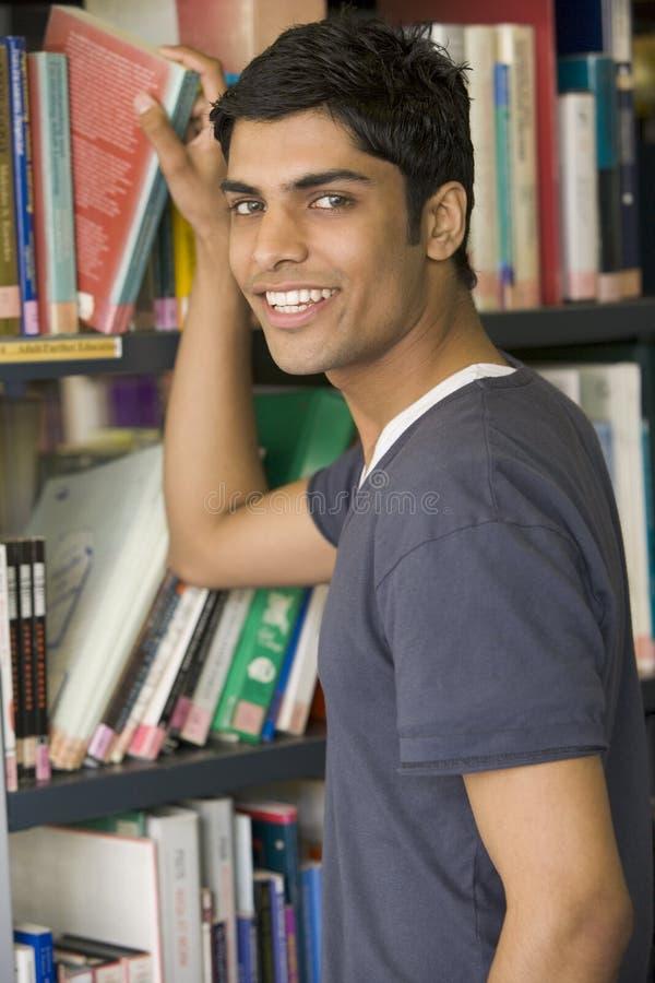 Estudante universitário masculino que alcanga para um livro da biblioteca fotografia de stock royalty free