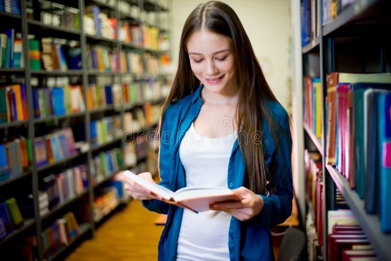 Estudante universitário na biblioteca imagens de stock royalty free
