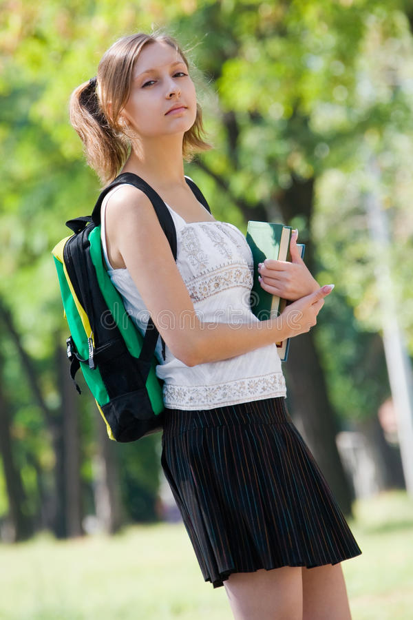Estudante universitário novo com trouxa e livros foto de stock