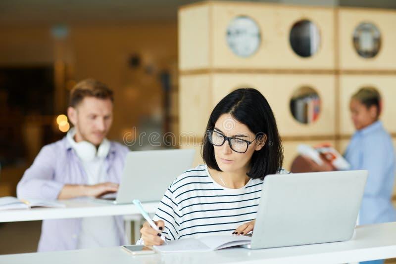 Estudante universitário ocupada que prepara o projeto na biblioteca imagem de stock