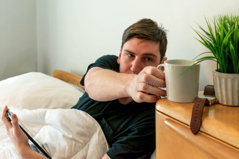 Estudante universitário que acorda e que come o café na cama imagens de stock