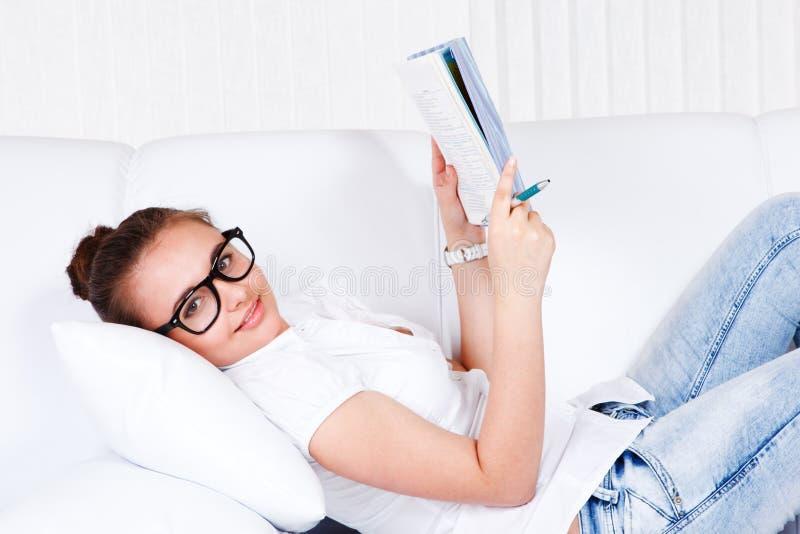 Estudante universitário que encontra-se no sofá foto de stock