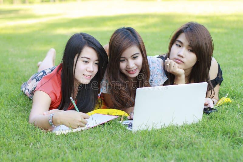 Estudante universitário que encontra-se para baixo no funcionamento da grama foto de stock