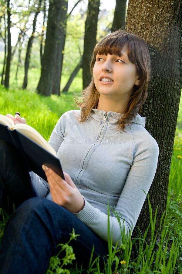 Estudante universitário que lê um livro fotografia de stock royalty free