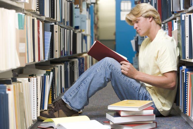 Estudante universitário que trabalha na biblioteca foto de stock