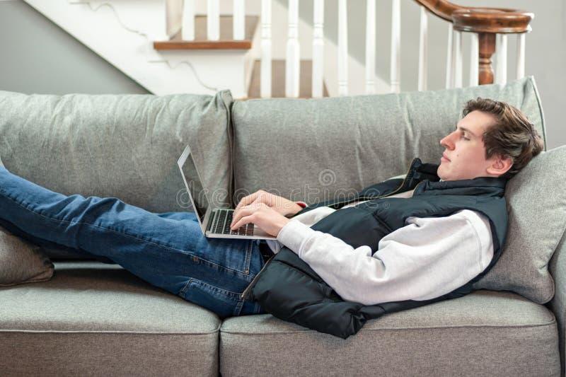 Estudante universitário que usa o portátil ao colocar no sofá imagem de stock royalty free