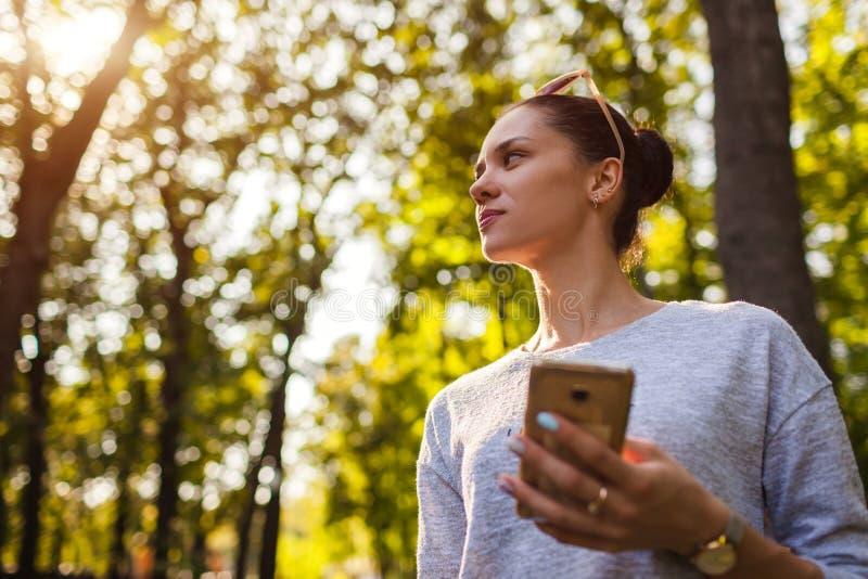 Estudante universitário que usa o telefone celular no parque Jovem mulher que guarda o smartphone foto de stock