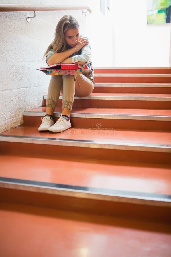 Estudante virado que senta-se em escadas foto de stock royalty free