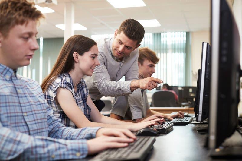 Estudante Working In Computer C da escola de Helping Female High do professor imagem de stock royalty free