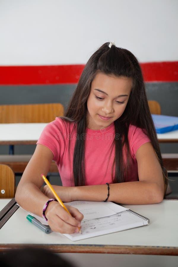 Estudante Writing In Book da High School na mesa foto de stock