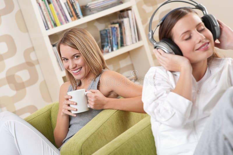 Estudantes - adolescente de duas fêmeas que relaxa na sala de estar foto de stock royalty free