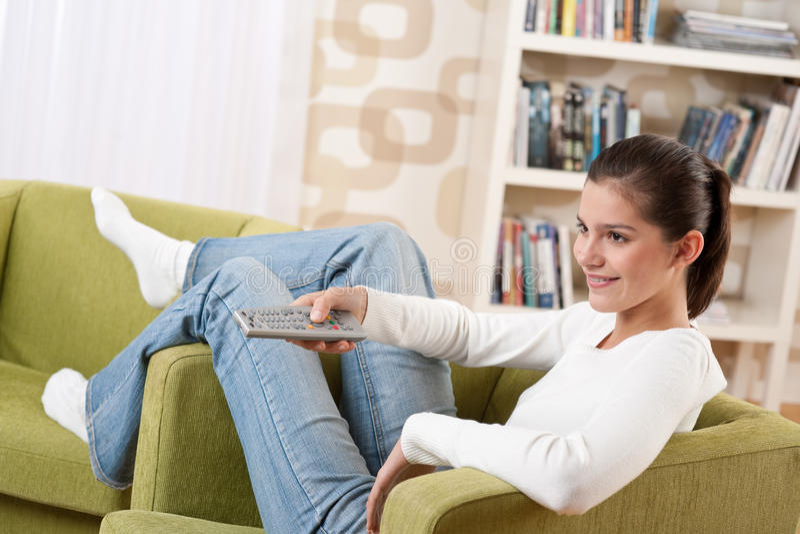 Estudantes - adolescente fêmea de sorriso que presta atenção à tevê fotos de stock