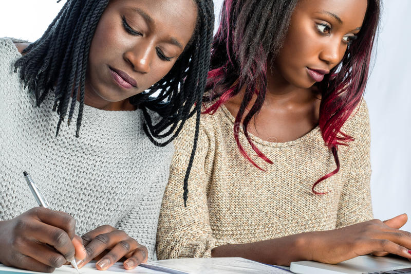Estudantes adolescentes africanos que trabalham junto na mesa fotos de stock royalty free