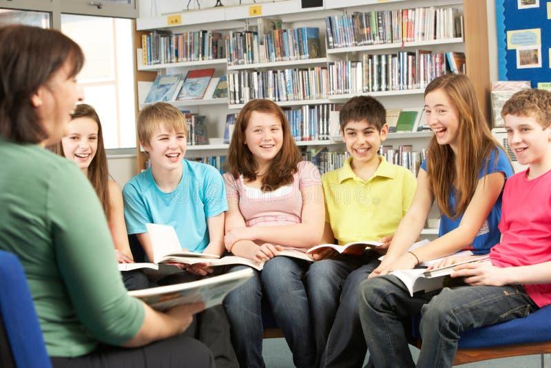 Estudantes adolescentes em livros de leitura da biblioteca imagens de stock
