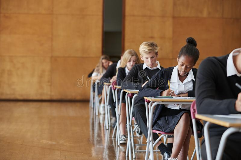 Estudantes adolescentes no exame de assento do uniforme na escola Salão foto de stock royalty free