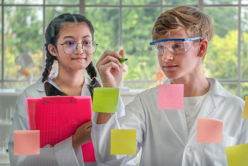 Estudantes adolescentes que escrevem em uma placa de vidro fotografia de stock royalty free