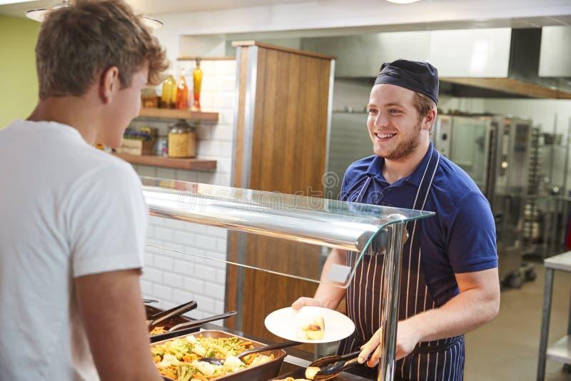 Estudantes adolescentes que são refeição servida na cantina da escola imagem de stock