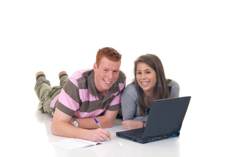 Estudantes adolescentes que trabalham no portátil imagem de stock