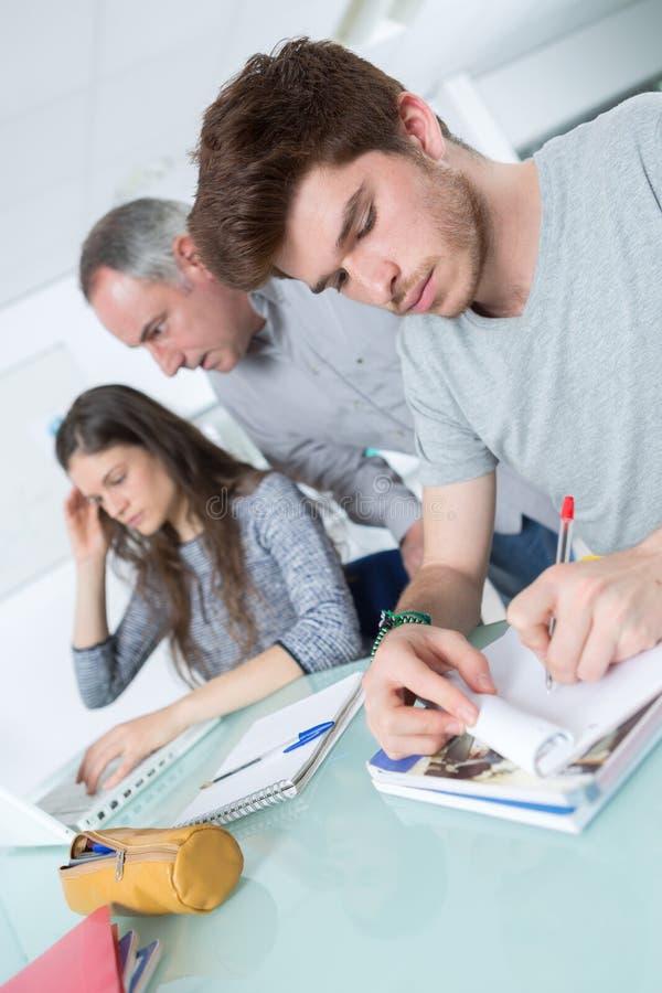 2 estudantes adultos atentos com o professor masculino na sala de aula imagem de stock