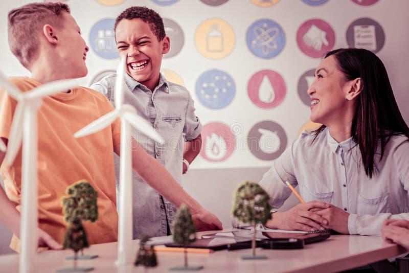 Estudantes alegres que riem abertamente durante classes adicionais fotos de stock