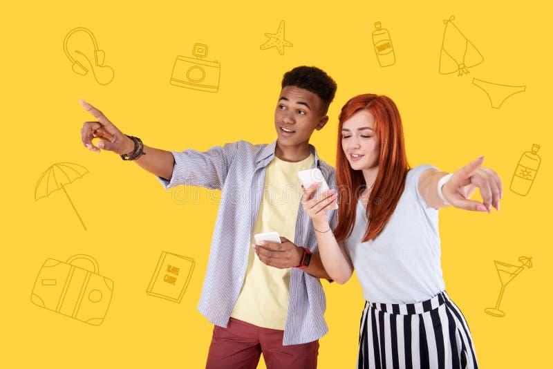 Estudantes alegres que sorriem e que apontam aos sentidos diferentes fotografia de stock royalty free