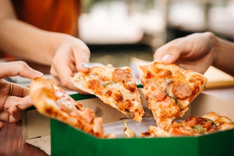 Estudantes asiáticos que comem comendo a pizza junto imagens de stock royalty free