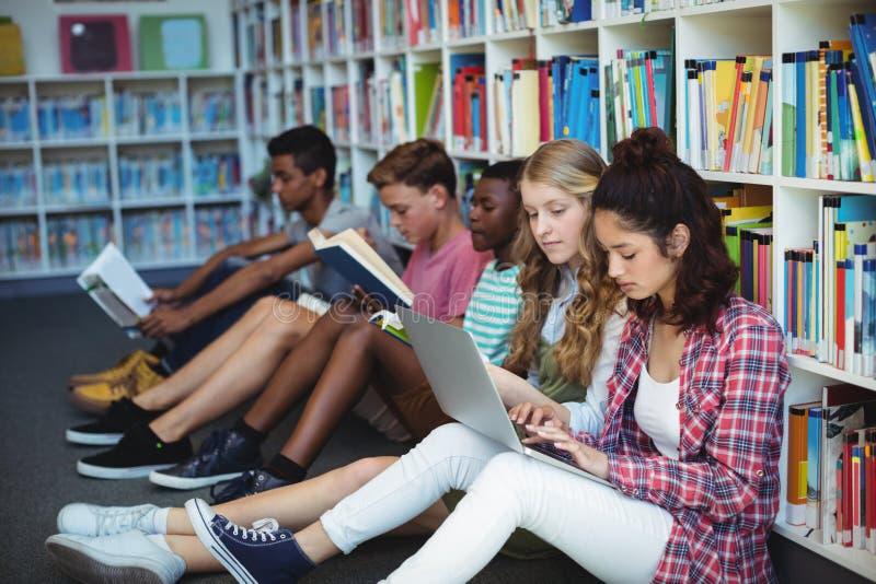 Estudantes atentos que estudam na biblioteca fotografia de stock