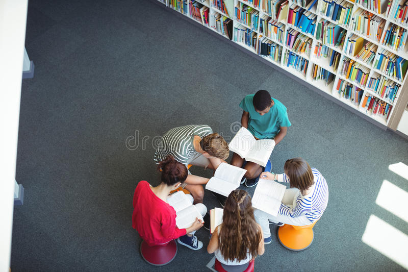 Estudantes atentos que estudam na biblioteca fotografia de stock royalty free