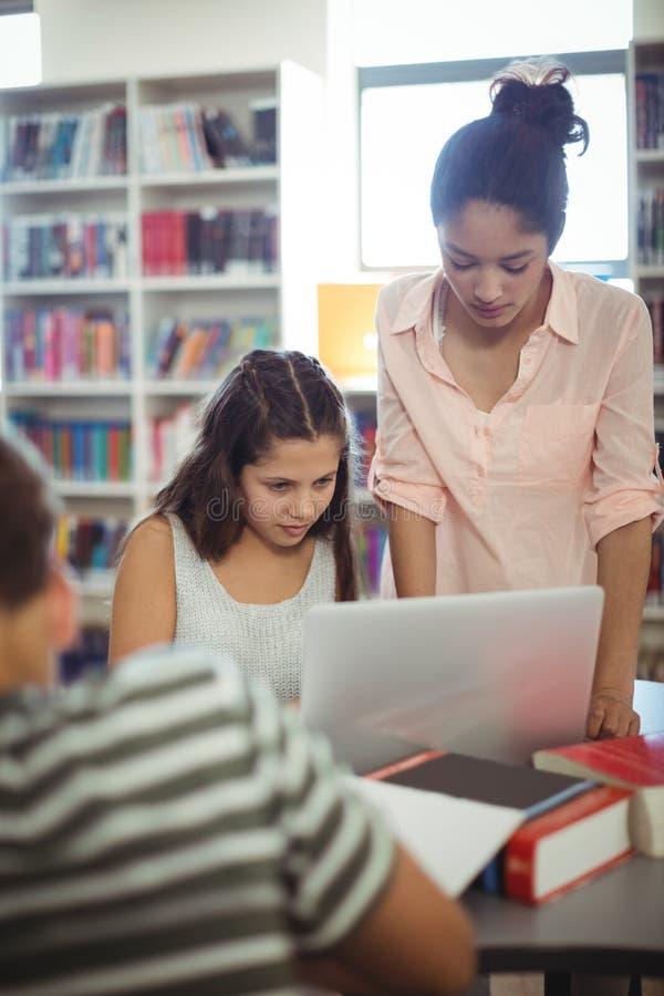 Estudantes atentos que usam o portátil na biblioteca fotografia de stock royalty free