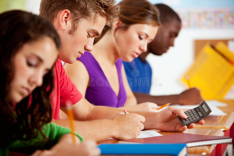 Estudantes: Calculadora de utilização adolescente masculina esperta para trabalhos de casa imagens de stock royalty free
