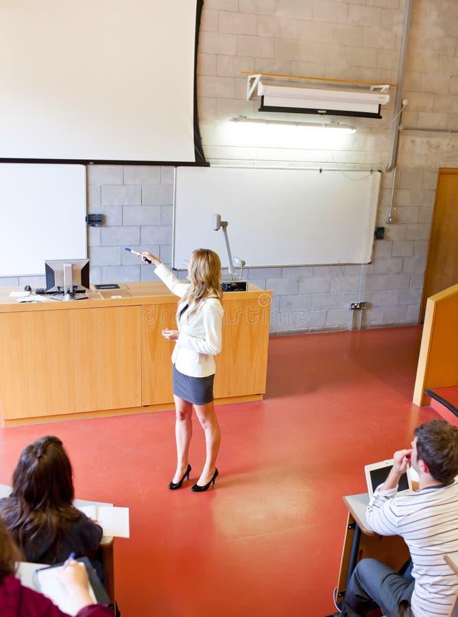 Estudantes cativados por seu professor bonito imagem de stock