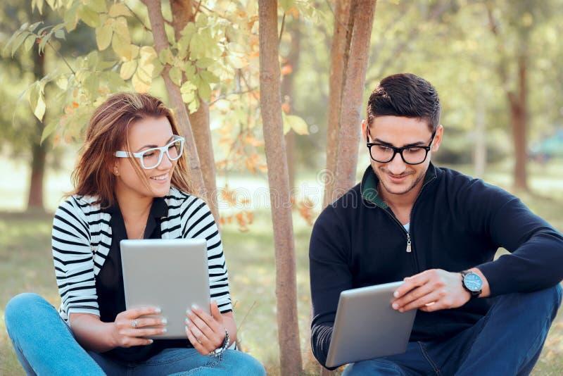 Estudantes com as tabuletas de Digitas que sentam-se na grama no campus universitário foto de stock