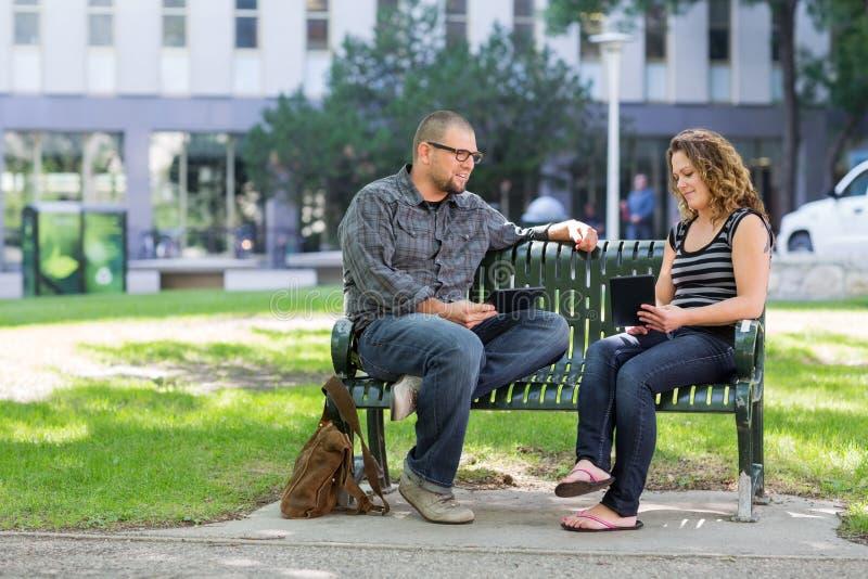 Estudantes com as tabuletas de Digitas que sentam-se no banco em foto de stock