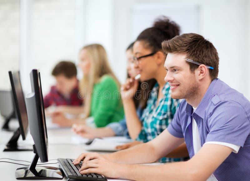 Estudantes Com Computadores Que Estudam Na Escola Imagem de Stock