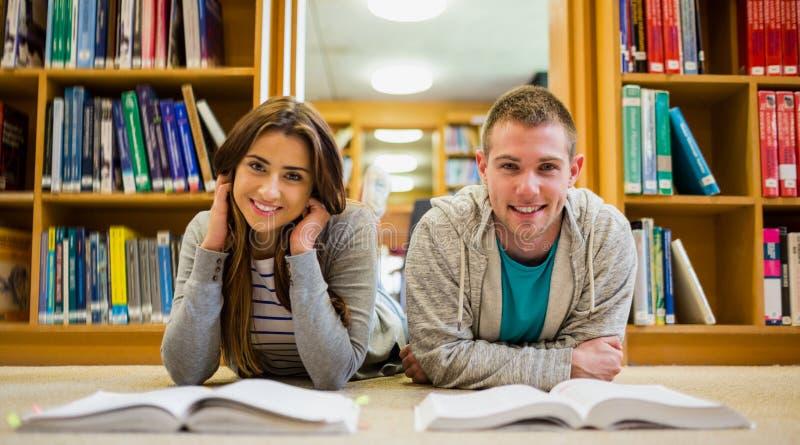 Estudantes com os livros que encontram-se no assoalho da biblioteca fotos de stock royalty free