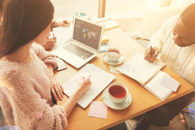 Estudantes concentrados que trabalham no projeto na economia foto de stock