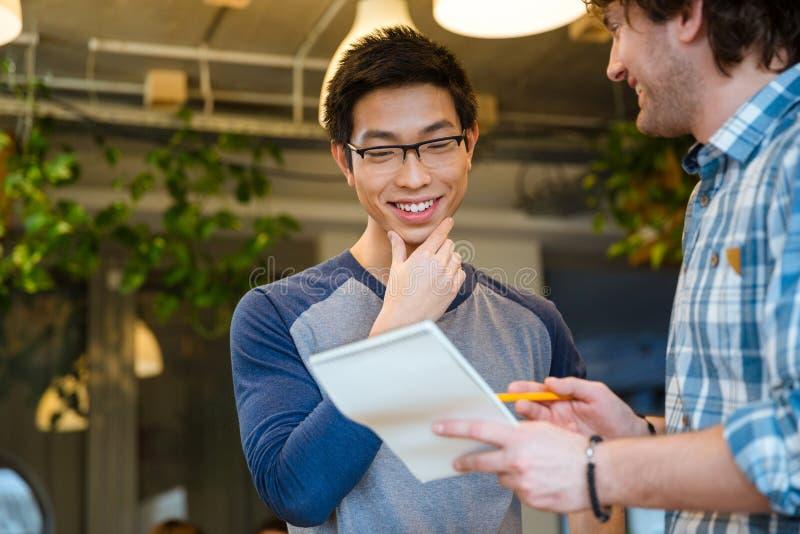 Estudantes consideráveis espertos alegres felizes que fazem anotações no bloco de notas junto imagem de stock royalty free