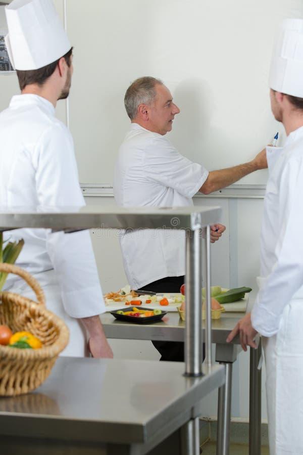 Estudantes culinários que aprendem como misturar a massa na cozinha fotos de stock
