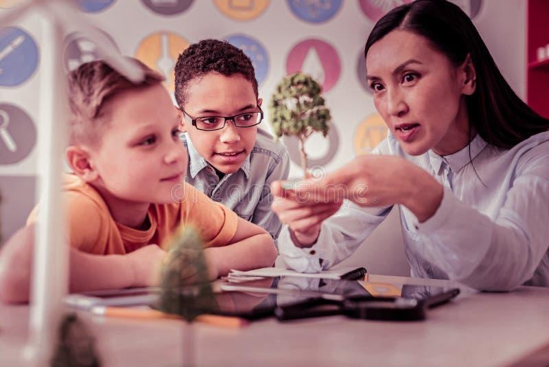 Estudantes curiosos que olham atentamente no modelo nas mãos do professor fotos de stock royalty free
