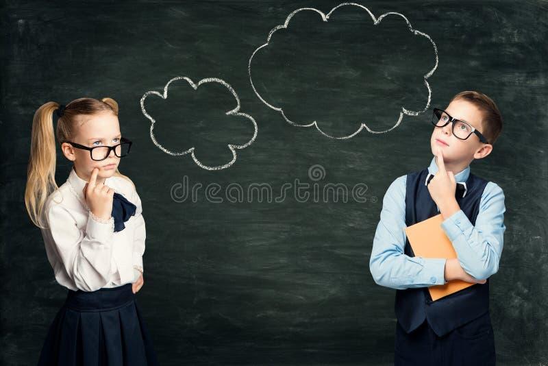 Estudantes das crianças que sonham a escola, tração no quadro-negro, pensamento esperto do giz da bolha dos alunos fotografia de stock royalty free