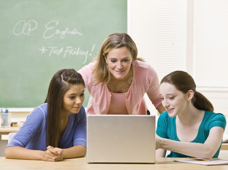 Estudantes de ajuda do professor no portátil fotos de stock