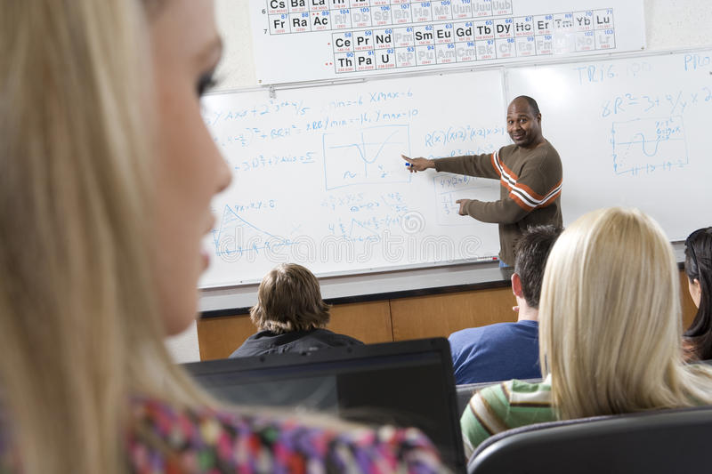 Estudantes de ensino do professor masculino na sala de aula foto de stock