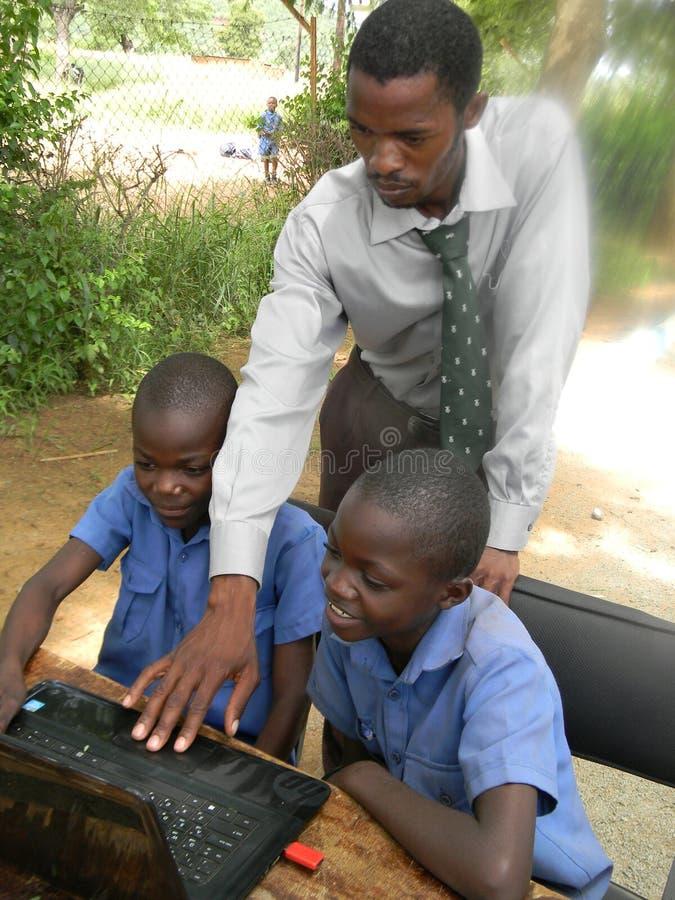 Estudantes de ensino do professor para usar um computador fotografia de stock