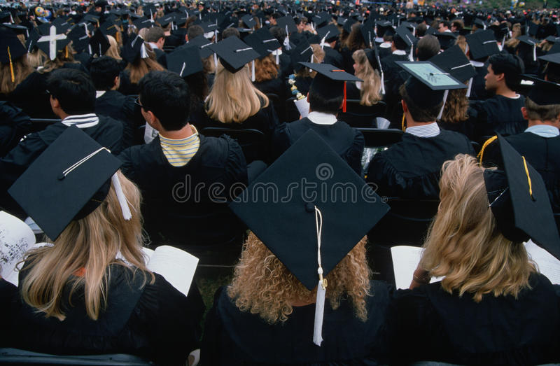 Estudantes de graduação no tampão e nos vestidos imagens de stock royalty free