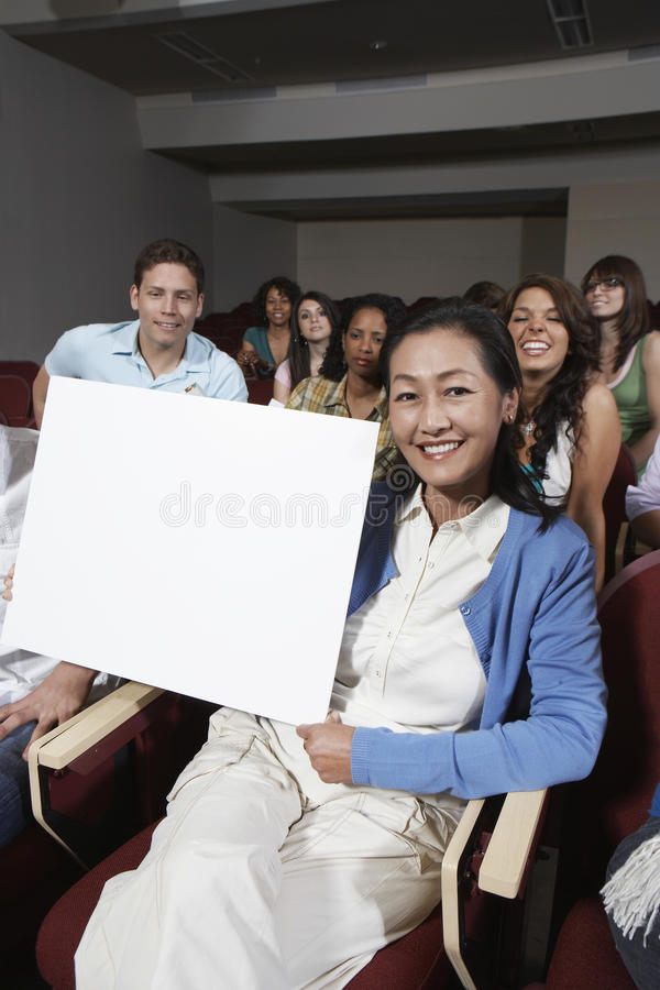 Estudantes de Holding Billboard With do professor no fundo fotos de stock royalty free
